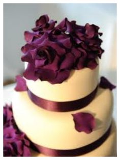 Plum wedding cake with falling flower petals