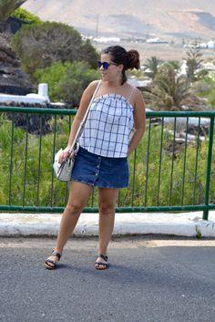 Look con falda vaquera y top de cuadros.