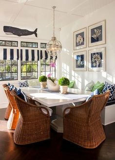Cottage breakfast nook features a navy sea prints over a built-in bench facing a white dining ... by DeeDeeBean
