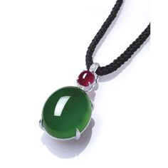 A HIGHLY IMPORTANT JADEITE, RUBY AND DIAMOND PENDANT NECKLACE  Suspending a thick high-domed jadeite cabochon of vivid emerald green colour and high translucency, surmounted by a cabochon ruby and a brilliant-cut diamond spacer, to the length adjustable black cord, mounted in 18k white gold