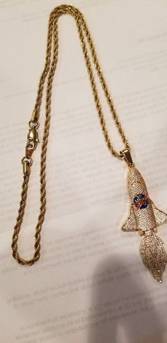YRN gold chain with rocket pendant