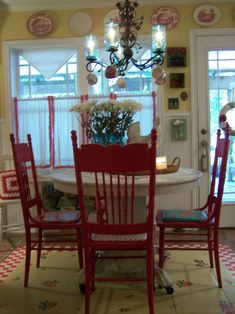 adorable breakfast nook.  my grannie - with her love of red - would have liked this!  notice the teacups hanging from the chandelier.  this photo got the wheels turning in my own head.  i painted my kitchen last year and haven't yet grown to love it.  still have some itches for that room that i need to scratch.  good inspiration here.