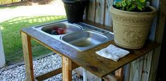 Outdoor utility sink using old kitchen sink and garden hose as water source
