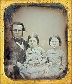 father and 2 girls with papier-mache doll