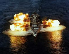 aerial bow view of the New Jersey (BB-62) firing its nine 16-inch/50 caliber guns simultaneously, 30 Dec 1986.