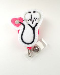 This retractable ID felt badge holder features a white and pink EKG stethoscope felt applique. It also features a pink heart. Sits on a hard plastic badge reel - you choose the color! If you wear a uniform or are required to wear a name badge/ID badge at work and you want to add a little
