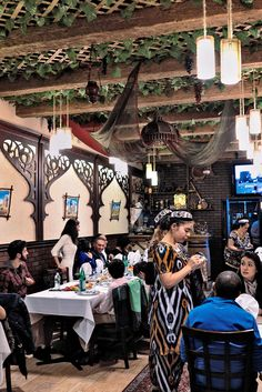 Inside is an arbor, with dangling bunches of grapes and leaves peeking through a trellis on the ceiling. Scenes from the Silk Road are painted on sheepskin and tied to frames made of crossed branches. (Photo: An Rong Xu for The New York Times)
