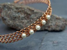 Each wire in this bracelet is wrapped and hammered into place to ensure strength and uniform spacing. Another smaller wire holds beautiful pearls in