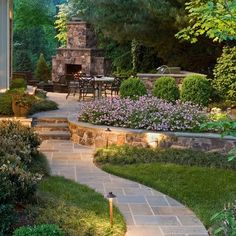 Gorgeous landscaping on a slight slope with fieldstone walls and fireplace and a flagstone path.