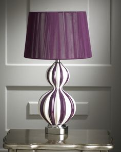 This new marble aubergine and white table lamp is a new addition to our lighting range. The base has a aubergine and white base vertically striped glass type shape with a slim waist, seated on a discreet chrome effect section. The lamp is complemented by a plain aubergine shade. The lamp has a standard fitting and is supplied without a bulb.