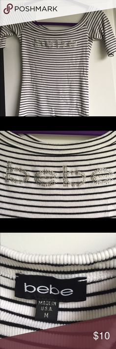 Black and white Bebe top White with black pinstripes, crystal Bebe (all crystals intact), half sleeve, ballet neckline. Size M. Excellent condition, free of holes, snags, and stain. Smoke free home bebe Tops Tees - Short Sleeve