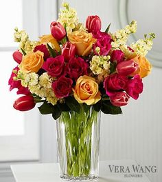 The Beauty and Grace™ Bouquet by Vera Wang. Displaying a refreshing sense of color and sunlit sophistication, this bouquet of fuchsia tulips, peach roses, pale yellow stock and hot pink spray roses are presented in a modern clear glass vase to delight your special recipient with its eye-catching demeanor.   #denverflorist #denverflowers #denverflowerdelivery
