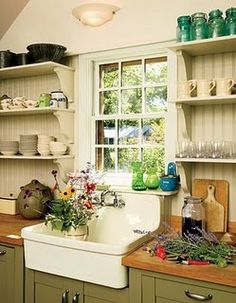 Farmhouse Kitchen...love the sink & green & cream colors on the open shelves and cabinets.