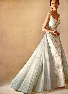 Model in beautiful white satin evening gown embroidered in silver and tufts of pale blue tulle, full blue tulle train falls from the back, by Lanvin-Castillo, photo by Pottier, 1952