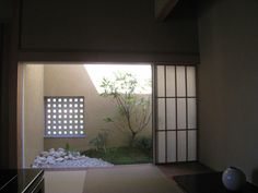 Small exterior garden with typical walled enclosure, viewed from washitsu room.