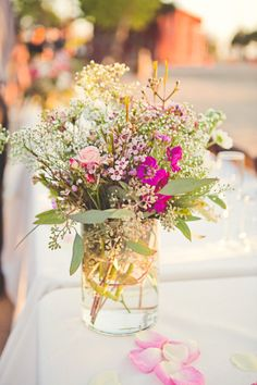 cheaper centrepiece idea, lots of florist filler flowers used together. Creates a wild flower rustic look too.