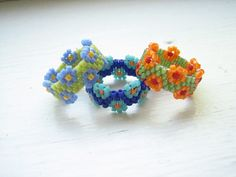 Three (3) beaded flower rings in varying colour combinations.. I made these cute colourful rings with Japanese glass Delica beads and nylon bead thread. They are NOT stretchy! Size 4.