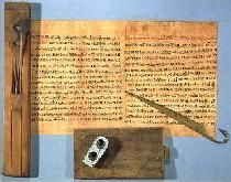 A scribe's tools: a wooden palette with storage for reed pen, a stone inkwell shaped like a Shennu (cartouche), a wooden writing board, and a metal scraper on tip of a used piece of papyrus. 18th dynasty. Ancient Egypt. Louvre museum.
