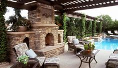 Rustic stone outdoor fireplace and outdoor lounge next to pool
