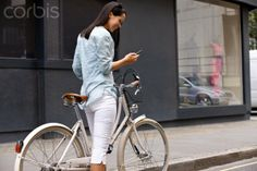 Young Woman On Bicycle, Using Mobile Phone