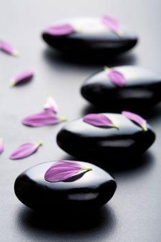 Ahhh... massage stones + petals! (Olga Miltsova | depositphotos)