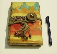 Bright cotton fabric and macrame cord and tie around a handmade button.  Covers of this journal are made with laminated plywood.  The macrame knotting has brown pony beads.  Yellow, orange, red and some aqua and gold are the beautiful colors on this handmade journal