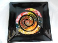 This one-of-a-kind dish is created using a screen melt technique. We take glass in assorted sizes and colors and melt them through a stainless steel screen in the kiln for  8-10 hours, with temperatures reaching 1600 degrees. We like the screen melt method for two reasons: it produces uniquely intricate patterns not possible any other way and it gives us the chance to repurpose small scraps of glass.  The resulting glass was then cut into a nautilus-like spiral and fused again, this time on…