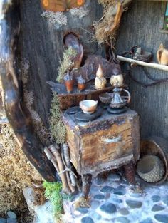 """The Fairy Treehouse, Kitchen, Little Forest Stove, Print (Photography) by Debbie and Mike Schramer The detail photo of the Treehouse kitchen shows the charming workmanship of this little stove, only about 6"""" tall, created from bark, pods and moss. Tiny little pots and pans made from pods, only an inch tall are set on the stovetop warming a wonderful meal from the elf's garden. A little gathering of tiny twigs used to keep the fire going in the woodland stove are set next to this enchanting…"""