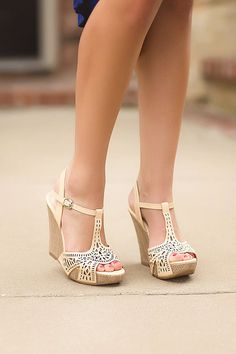 Front angled view of woman wearing natural colored wedges with laser cut detail and adjustable ankle strap