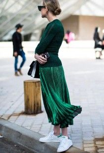 A green pleated skirt, sweater and sneakers, are the perfect combination for a casual outfit
