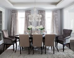 Pale gray/blue wall color. Nickel bar cart, velvet gray end chairs and traditional oval table. Floor to ceiling draperies with subtle geometric patter. Contemporary nickel chandelier with silver trimed shades.