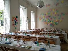 The ballroom , set whimsically, with simple party balloons and paper decor, for a hundred.