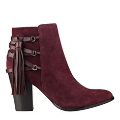 Pointed toe bootie with stacked heel, fringe detail and polished hardware.