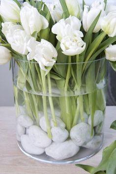 Deko mit Tulpen weiße Tulpen weiße Steine durchsichtiges Glas elegantes Arrangement