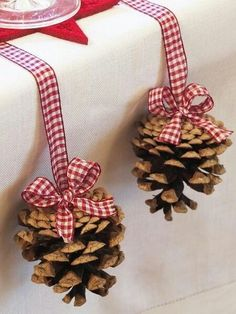 pinecones suspended from ribbon bows at the ends of a table runner
