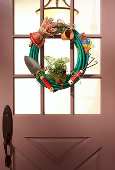 A whimsical garden hose wreath hangs on a front door.  THIS WOULD MAKE A GOOD HOUSE WARMING GIFT.