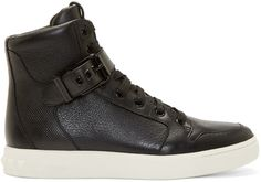 High-top leather sneakers in black. Round toe. Black hardware. Lace-up closure. Extended padded bellows tongue. Adjustable pin-buckle strap at vamp with lizard skin texture stamped throughout. Rubber sole in ivory white with raised logo and pyramid studs at heel. Tonal stitching.