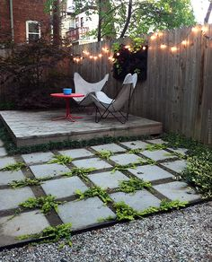 Square pavers, spacing between, small raised wooden deck, lights strung on the fence...
