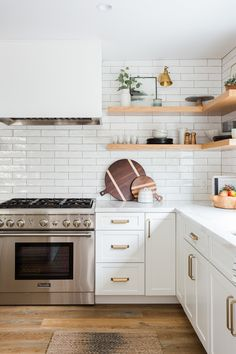 White kitchen cabinets, white subway tile, and light wood open shelving really make this beautiful, neutral kitchen. White Kitchen Cabinets, Kitchen Shelves, Kitchen Tiles, Kitchen Countertops, Kitchen Decor, Kitchen Wood, Kitchen White, Floors Kitchen, Kitchen With Subway Tile