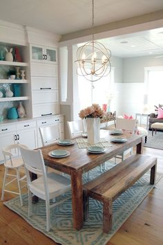 notice the wood table with the bench in a white setting #diningroomlighting