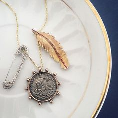 Super excited about this #antique #sterling #medal #pendant I just picked up (shown here with my handmade #feather pendant with #pavé #ruby stem, available in my shop). I just love the #handmade, nautical-inspired ship's wheel style border ⛓⚓️ Still not sure whether to keep it or sell - can anyone guess what's on the other side? ⁉️⛵️⁉️ #antiquejewelry #jewelsforgypsies #showmeyournecklace #lovegold