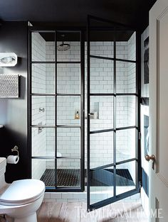 Black steel-framed doors enclose the oversized shower stall. The custom Nero Marquina basket-weave shower floor with Carrara dots is from Waterworks. - Photo: Emily Gilbert / Design: Jenny Wolf