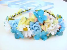 Our flower crown has white daisies and shades of turquoise blue, aqua blue and baby blue hydrangea and blue roses. Touches of yellow and pale pink flowers throughout. #daisyflowercrown