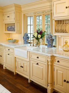 Combines clean lines with dental mold, apron sink, and plate racks. Love the different depths of the cabinetry.