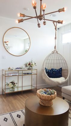 Gorgeous modern room with brass chandelier, large round mirror, gold console table, and especially that hanging basket chair // theglitterguide.com