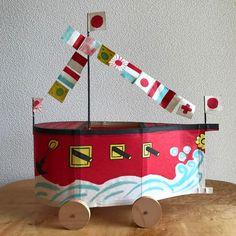 Vintage Japanese Paper Folk Art Battle Ship Toy, Tottori.  紙軍艦 明治三十七、八年の日露戦争の時、日本海の大海戦ののち出来たものです。 大正十二、三年頃迄は形も今よりずっと大きく、一メートル位もありました。 舗装されていない石ころのはみ出した道を、男の子は「グンヤラセー グンヤラセー」と掛け声をかけ、勇んで曳いて歩きました。 電灯のない時代の事ですから夏の風物としてはゆかいなものでした。  柳屋本店 田中 達之助  以上、説明書より。  鳥取の柳屋による、古い紙軍艦。