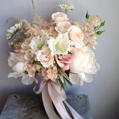 bouquet of ivory peonies, blush spray roses, white scabiosa, jasmine vine, pale pink astilbe, and blush stock flowers wrapped in ivory ribbon with the stems showing.