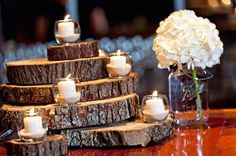 nfuse your wedding's atmosphere with an earthy elegance by arranging tea light candles over layers of wooden slabs. The result? A unique blend of romance and rustic appeal.