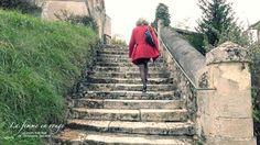 Jeune femme qui monte un escalier vue de dos. Habillée en manteau rouge, jupe droite noire et chaussures à talons.