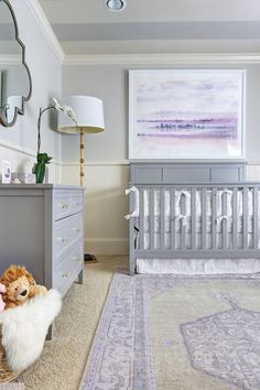 neutral child's bedroom with gray, purple and white accents, white wainscoting